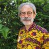 Ds Flip Beukenhorst, voor de gelegenheid gekleed in een Rwandees hemd, dat ter plekke op maat werd gemaakt door een naaister op een markt in Rwanda (Afrika). In zijn tijd als jeugdpredikant begeleidde hij met een groep Nederlandse en Belgische protestantse jongeren een ZWO-ontmoeting met Rwandese jongeren van de Eglise Presbytérienne au Rwanda.