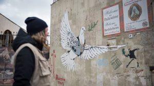 1 March 2020, Bethlehem, Palestine: A participant in the Ecumenical Accompaniment Programme in Palestine and Israel looks at the drawing of a dove carrying an olive branch while wearing a bullet proof vest and the mark of a sniper's aim, on a wall in Bethlehem.